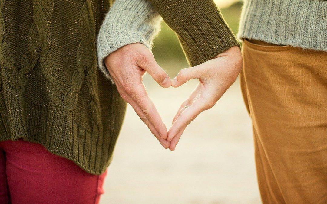 Detalle de las manos de una pareja al aire libre formando un corazón al darse la mano. Las dos personas van vestidas con jersey de invierno manga larga, una color verdoso y la otra color gris azulado. Una persona viste vaqueros rojos y la otra vaqueros marrones anaranjados.